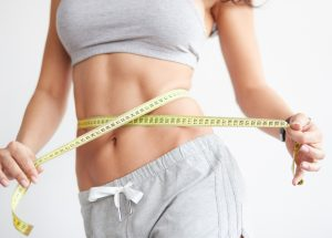 Sportliche Frau die sich ein Maßband um den Bauch hält